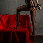 Beautiful Sexy Lady In Bdsm Outfit. Close Up Of Model With Hand In Bondage Near Red Sofa - Image poster