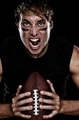 American football player screaming aggressive holding american football on black background. Strong