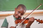 image of children playing  - Schoolboy playing the violin in a classroom - JPG