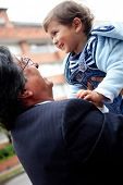 Young grandfather holding a child in the air and smiling - outdoors