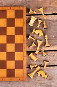 Chess Board And Chess Pieces, Top View. White Chess Figures Lying Near Chess Board On Rustic Wooden  poster