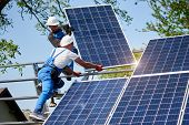 Two Workers Mounting Heavy Solar Photo Voltaic Panel On Tall Steel Platform On Green Tree And Blue S poster