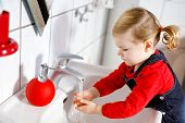 Cute Little Toddler Girl Washing Hands With Soap And Water In Bathroom. Adorable Child Learning Clea poster