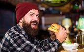 Hipster Hungry Man Eat Burger. Man With Beard Eat Burger Menu. Brutal Hipster Bearded Man Sit At Bar poster