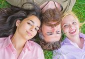 Man Bearded Hipster Lay On Grass With Two Girls Blonde And Brunette. Blonde And Brunette Lay On His  poster