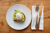 Grilled bread with guacamole and poached egg shot from above on wooden table poster
