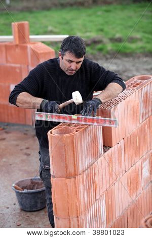 man erecting a brick wall