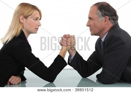 Businessman and woman arm wrestling