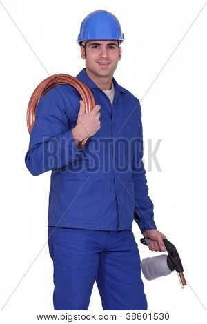 Plumber holding copper pipe and blow torch