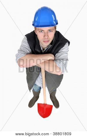 A male construction worker with a shovel.