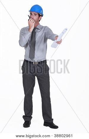 architect holding blueprints holding talkie-walkie