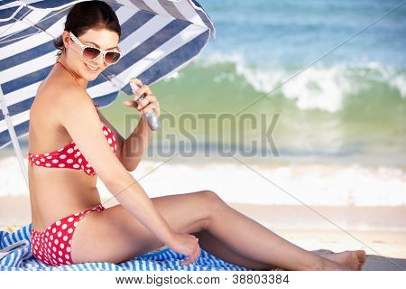 Woman Sheltering From Sun Under Beach Umbrella Putting On Sun Cream