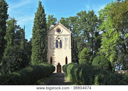 Charming baroque chapel lit sunset. Go to the chapel are ancient stage, covered with moss. The magnificent park in northern Italy
