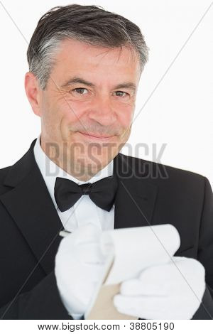 Smiling waiter looking into the camera while is writing something into the notebook