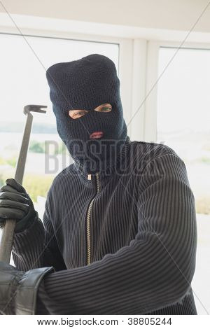 Robber holding a crowbar in his hands while he is inide of the house