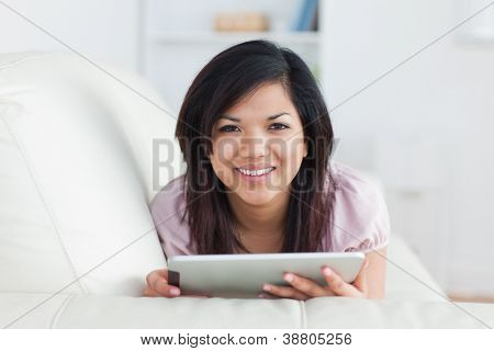 Woman smiling while resting on a couch and playing with a tablet in a living room