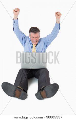 Hombre de éxito en el piso con su computadora portátil con los brazos en el aire