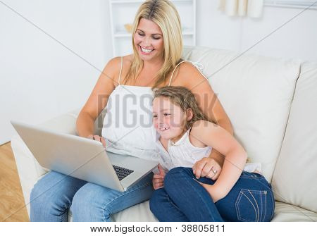 Laughing mother and daughter using notebook during resting on sofa