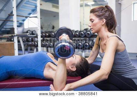 Female trainer helping female client lifting weights in gym