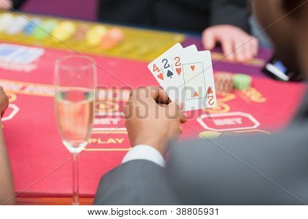 Man holding up poker hand in casino