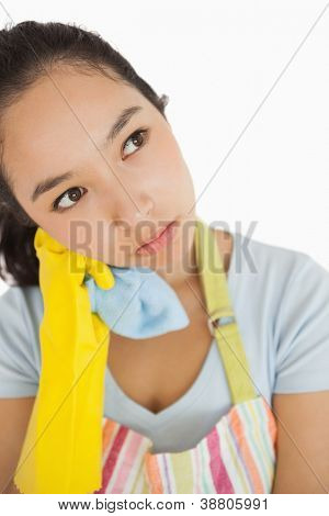 Overworked cleaning lady in apron and rubber gloves holding a rag