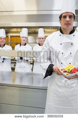 Chef presenting fruit salad with team standing behind him