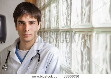 Smiling doctor leans against glass wall in hospital