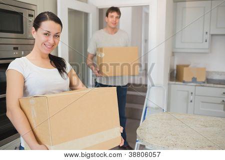 Jovem e mulher segurando caixas em suas mãos para realocar