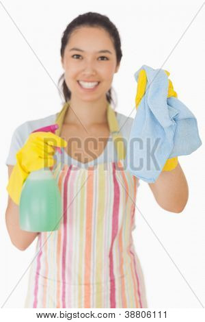 Smiling young woman holding up rag and spray bottle in apron and rubber gloves