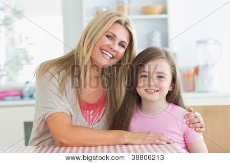 Mother and little girl smiling at the kitchen and embracing