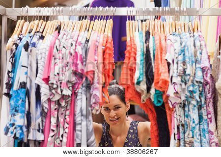 Woman standing behind a clothes rack of a store smiling