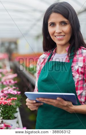 Woman doing inventory with laptop in working in greenhouse