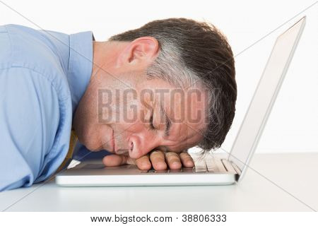 Businessman sleeping on his laptop on his desk