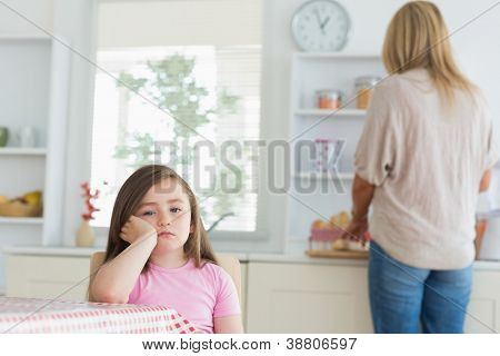 Little girl bored in the kitchen with mother working at counter