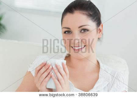 Smiling woman sitting in a living room on the couch and holding a mug