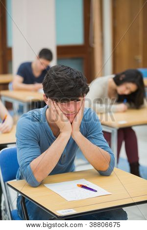 Student looking helpless taking an exam in exam hall of college