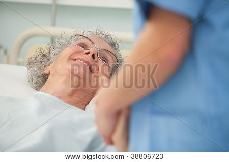 Elderly female patient looking up at nurse from hospital bed