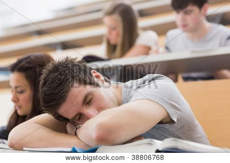 Student sitting at the lecture hall leaning on the table sleeping