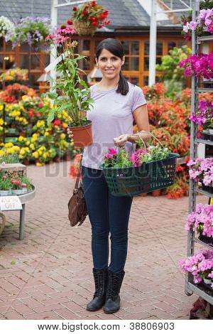 Woman carrying bag and plant shopping in garden center