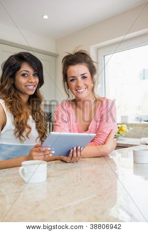 Happy girls with tablet computer having coffee in kitchen