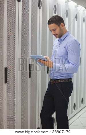 Technician doing maintenance with tablet pc in lighted hallway
