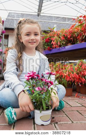 Little girl sitting on the path holding a flower in garden center