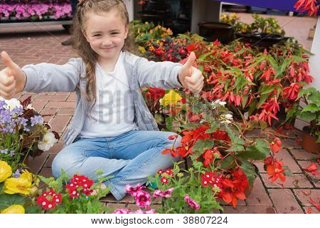 Little girl giving thumbs up while sitting on the floor with flowers around her