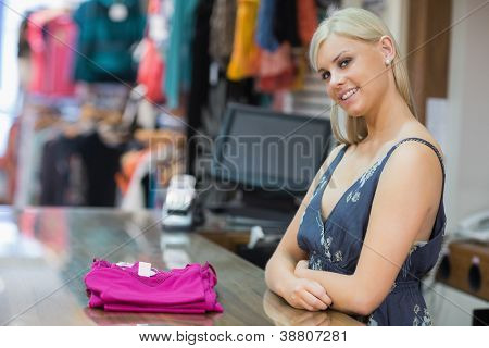 Woman standing behind the counter smiling with clothes folded on the counter