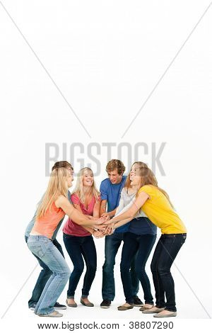 Group of friends about to cheer with their hands stacked smiling as they look at one another