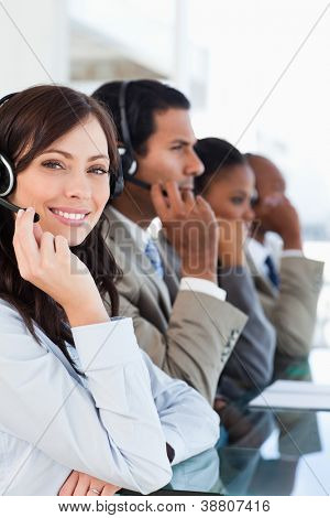 Young smiling call centre agent looking at the camera while working hard