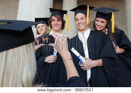 Close-up of a female graduate taking a picture of her friend in front of the university
