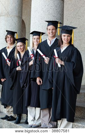 Happy smiling graduates posing in single line with columns in background