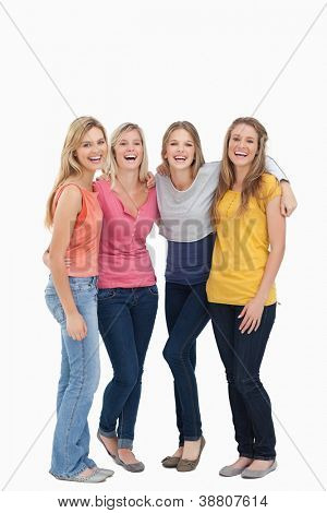 A full length shot of four girls holding each other as they smile and look at the camera