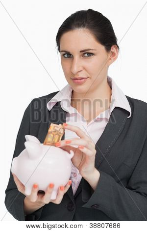 Brunette putting money into a piggy-bank against white background